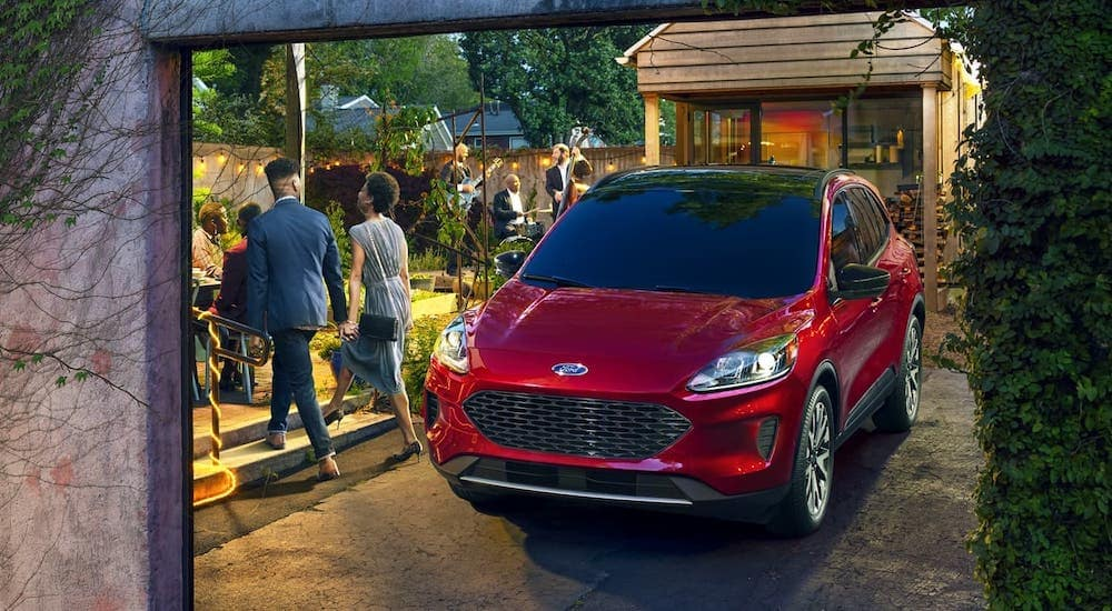 A couple is walking away from a red 2020 Ford Escape SE Hybrid and towards a party.