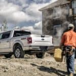 Construction workers are walking toward a silver 2020 Ford F-150 at a work site near Albany, NY.