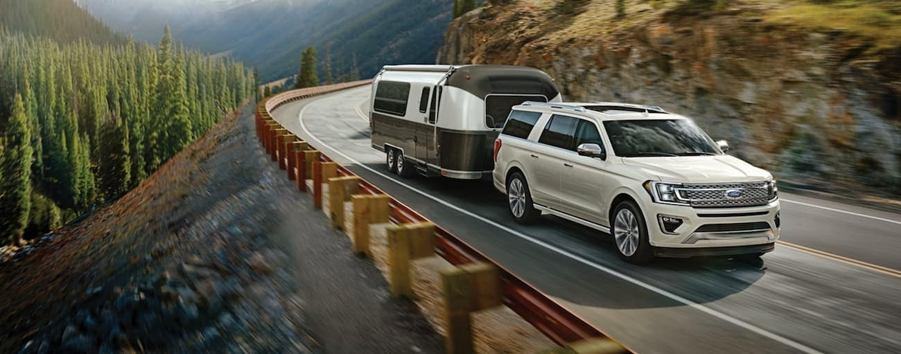 A white 2020 Ford Expedition is towing a camper on a winding mountain road near Albany, NY.