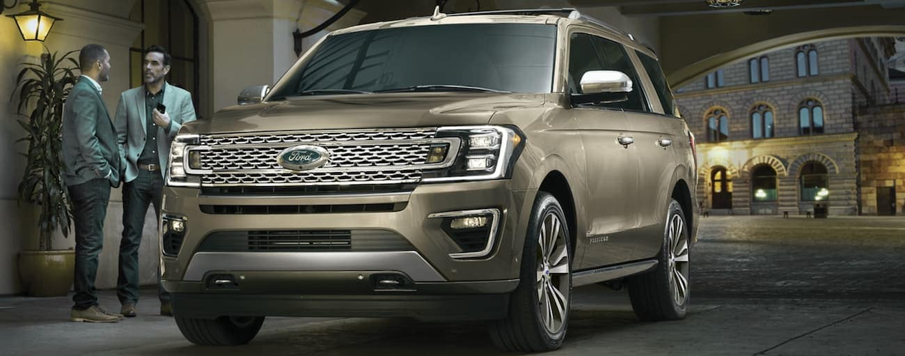 Two men are standing next to a tan 2020 Ford Expedition in front of a building at night.
