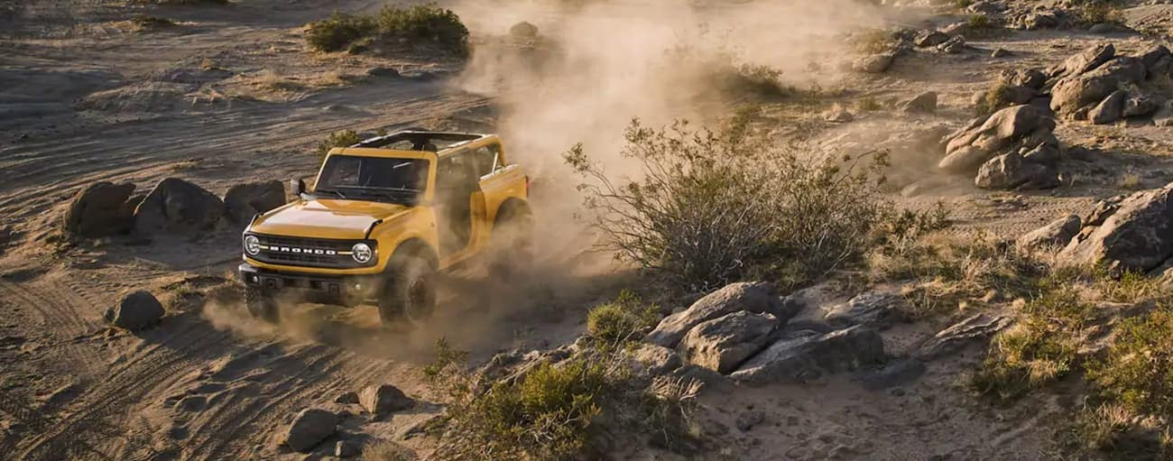 A yellow 2-Door 2021 Ford Bronco is off-roading on a dirt trail near Albany, NY.