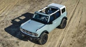 A light blue 2021 Ford Bronco is shown from an above angle on a dirt road.