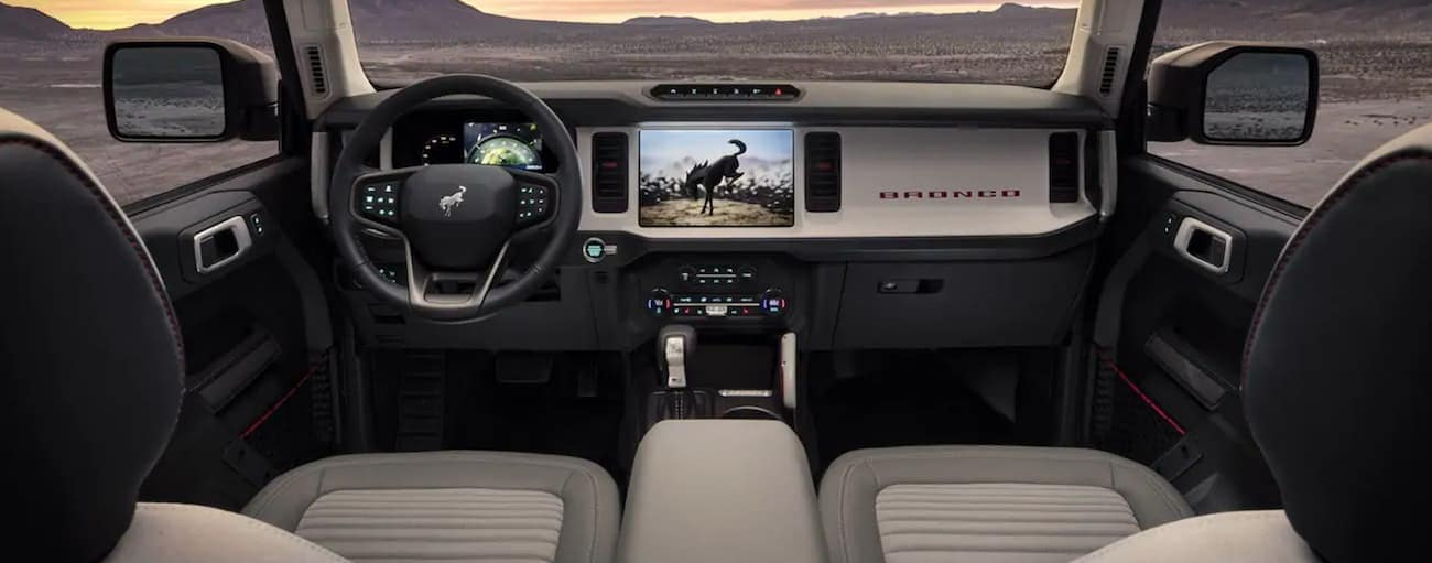 The white interior of a 2021 Ford Bronco is shown facing the dashboard.