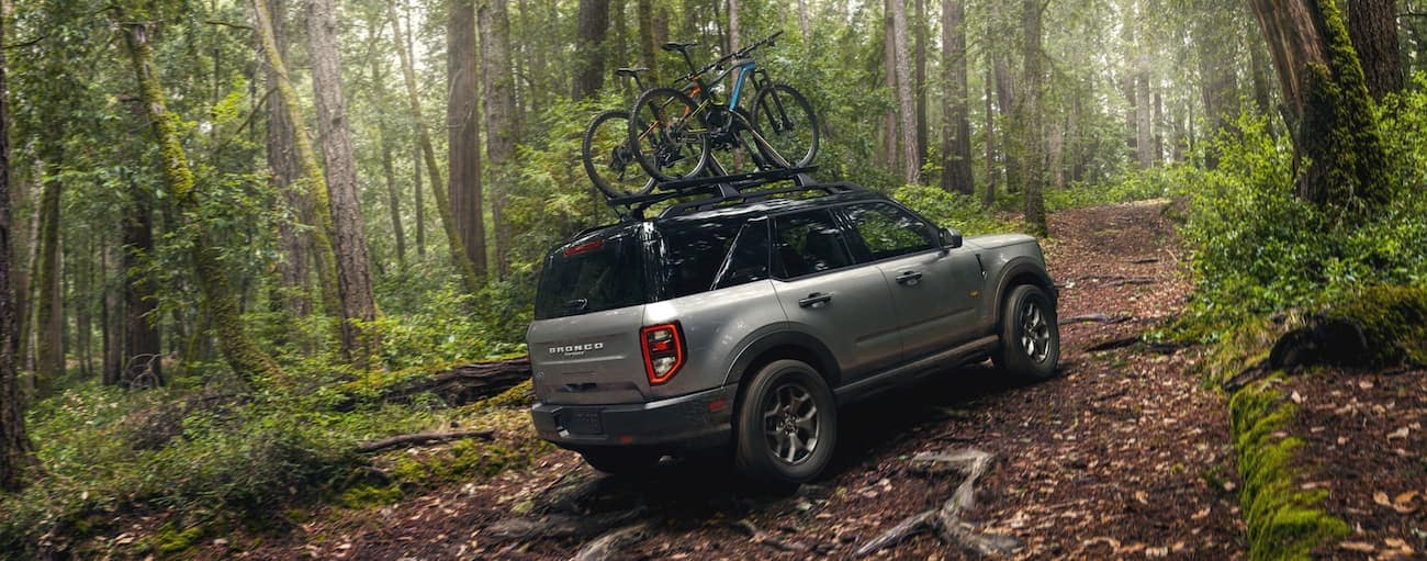 A grey 2021 Ford Bronco Sport is off-roading in the woods with bikes on the roof.