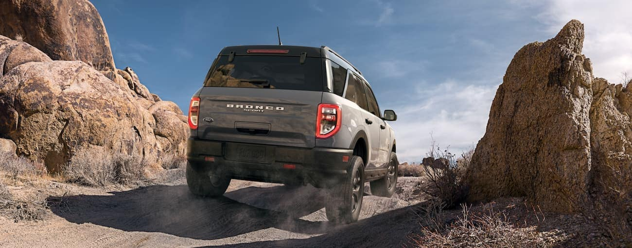 A grey 2021 Ford Bronco Sport is driving on a dirt trail in the desert, shown from the rear.