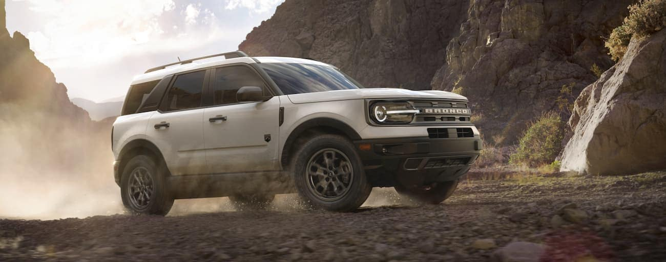 A white 2021 Ford Bronco Sport is kicking up dust while off-roading in front of rocky hills.