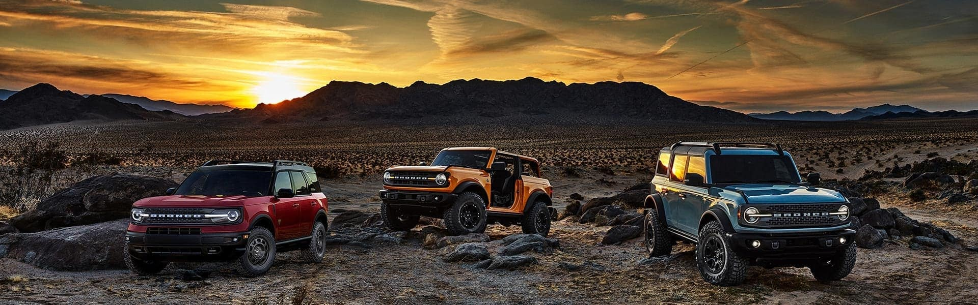The family of 2021 Ford Broncos is shown parked in a desert at sunset, including a blue 4-door Bronco, an orang 2-door Bronco with no roof or doors, and a red Bronco Sport.
