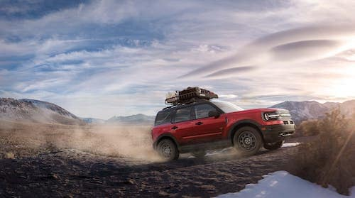 A red 2021 Ford Bronco Sport is driving with mountains in the distance.