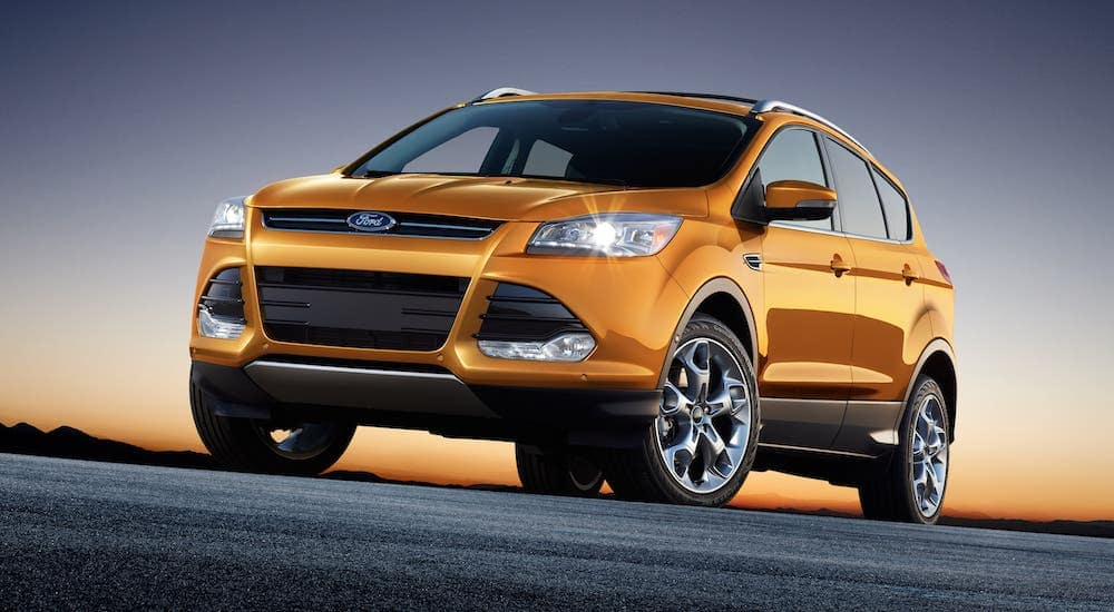 A orange used 2016 Ford Escape is shown from a low angle at sunset.