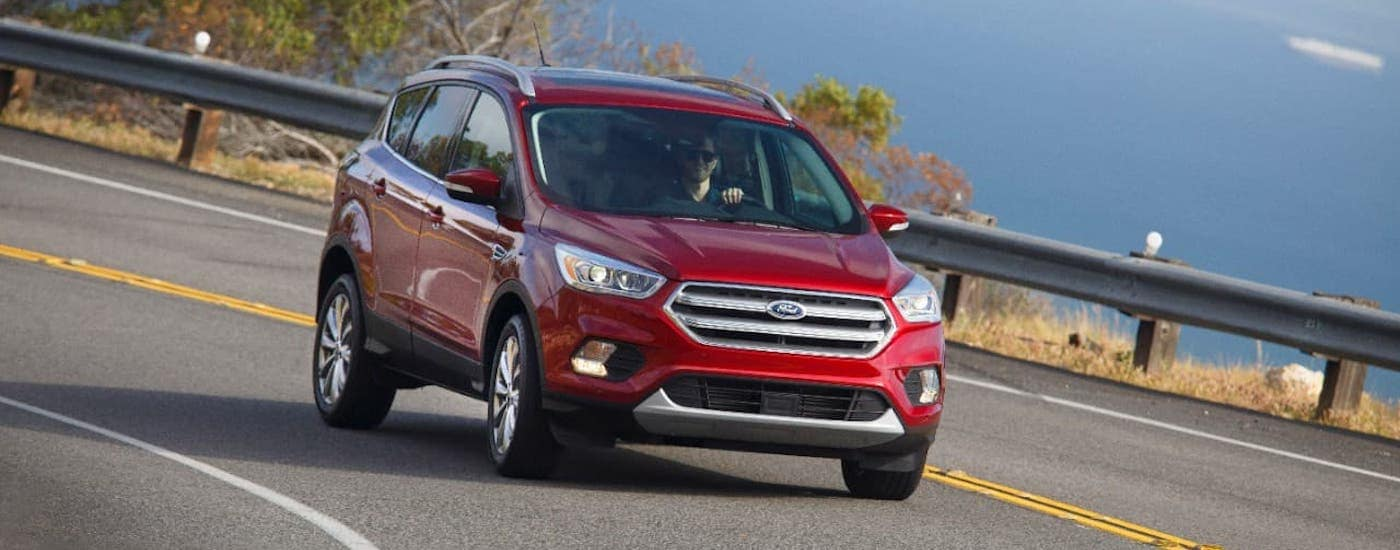 A red 2017 Ford Escape is driving along a coastal highway.