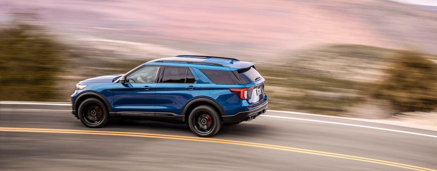 A blue 2020 Ford Explorer is driving on a highway against a blurry background.