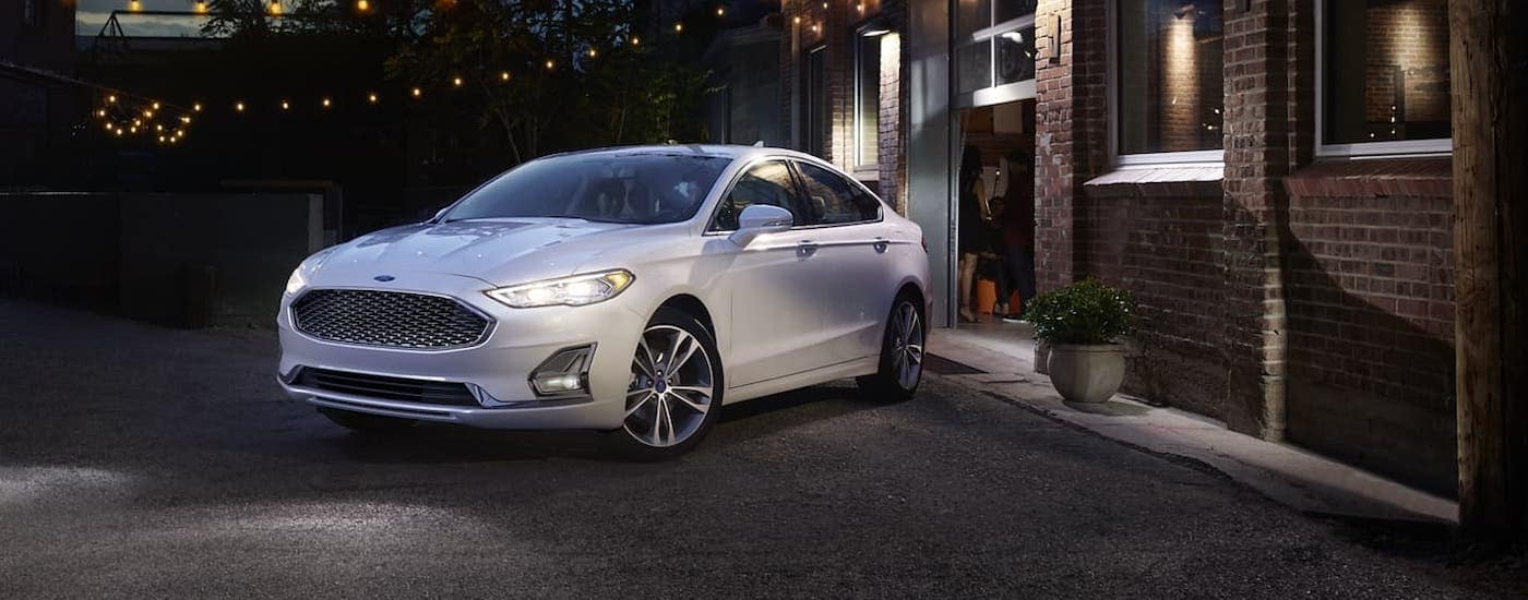 A white 2020 Ford Fusion is parked in front of a brick building in Albany at night after winning the 2020 Ford Fusion vs 2020 Chevy Malibu comparison.