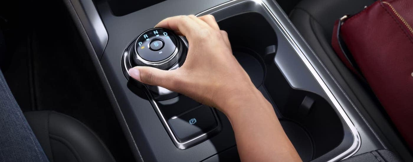 A closeup shows a hand using the shift knob in a 2020 Ford Fusion.