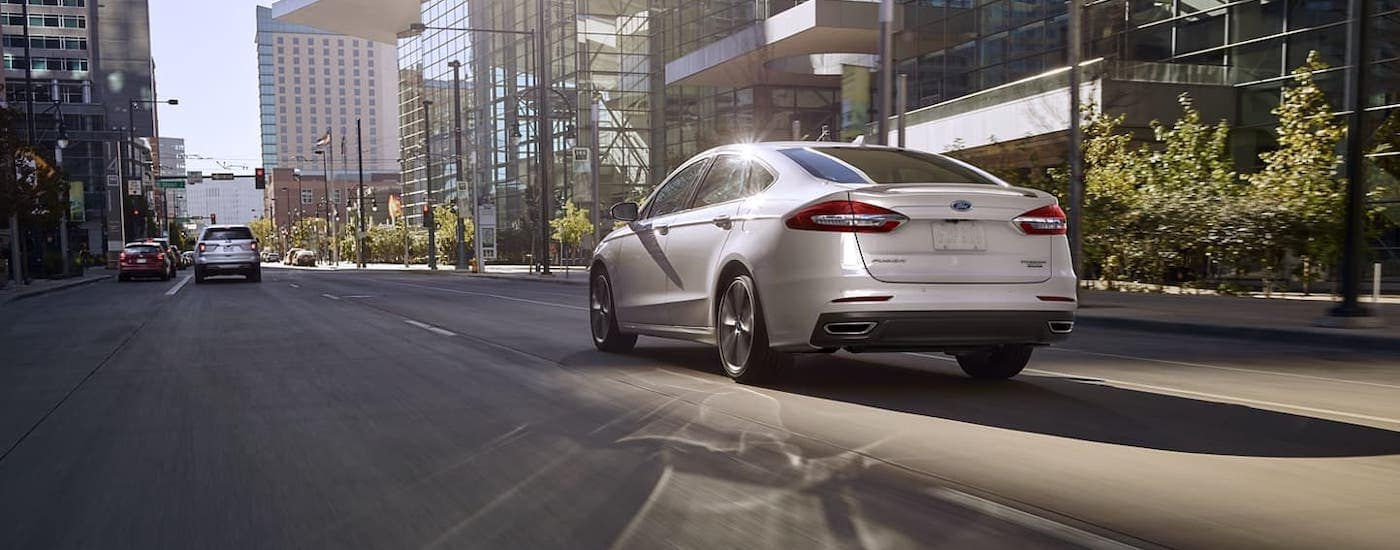A white 2020 Ford Fusion is driving on a city street after winning the 2020 Ford Fusion vs 2020 Kia Optima comparison.