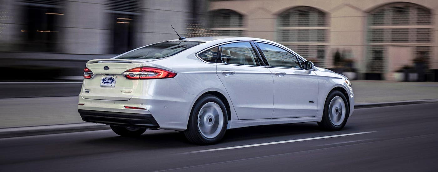 A white 2020 Ford Fusion is driving on a city street after winning the 2020 Ford Fusion vs 2020 Mazda 6 comparison.