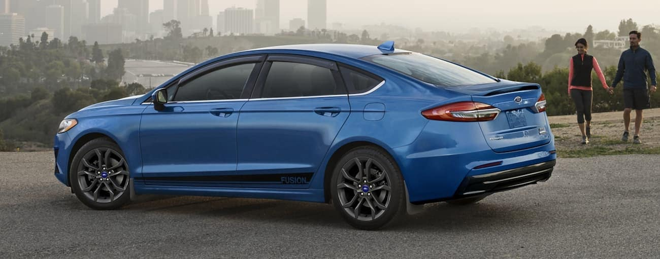 A blue 2020 Ford Fusion is parked with a foggy view of a city after winning the 2020 Ford Fusion vs 2020 Nissan Altima comparison.