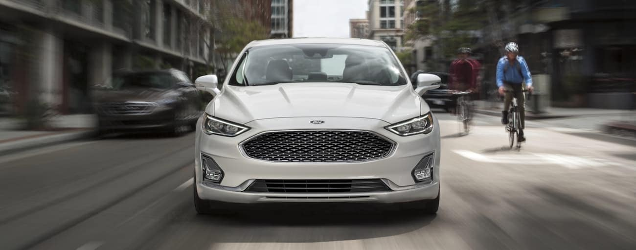 A white 2020 Ford Fusion is driving on a city street shown from the front, near Albany, NY.
