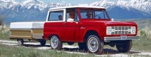 A red 1966 Ford Bronco is towing a camper in front of snow-covered mountain.