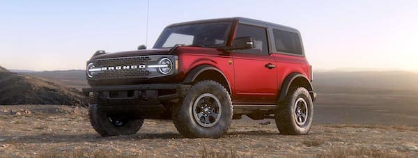 A red 2021 Ford Bronco is angled left in front of a desert.