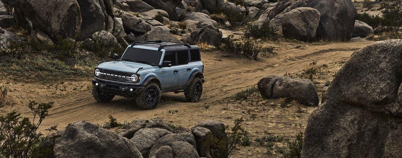 A light gray 2021 Ford Bronco is driving over rocks after winning the 2021 Ford Bronco vs 1966 Ford Bronco comparison.