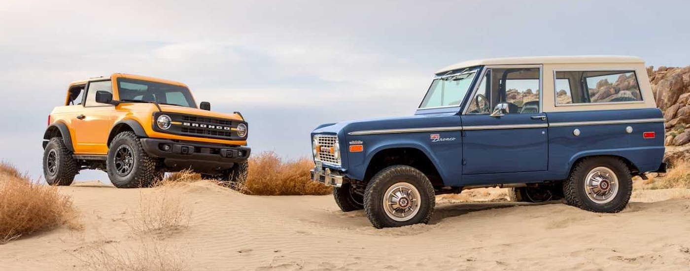 An orange 2021 Ford Bronco 2-door and a blue 1966 Ford Bronco are parked on a beach near Albany, NY.