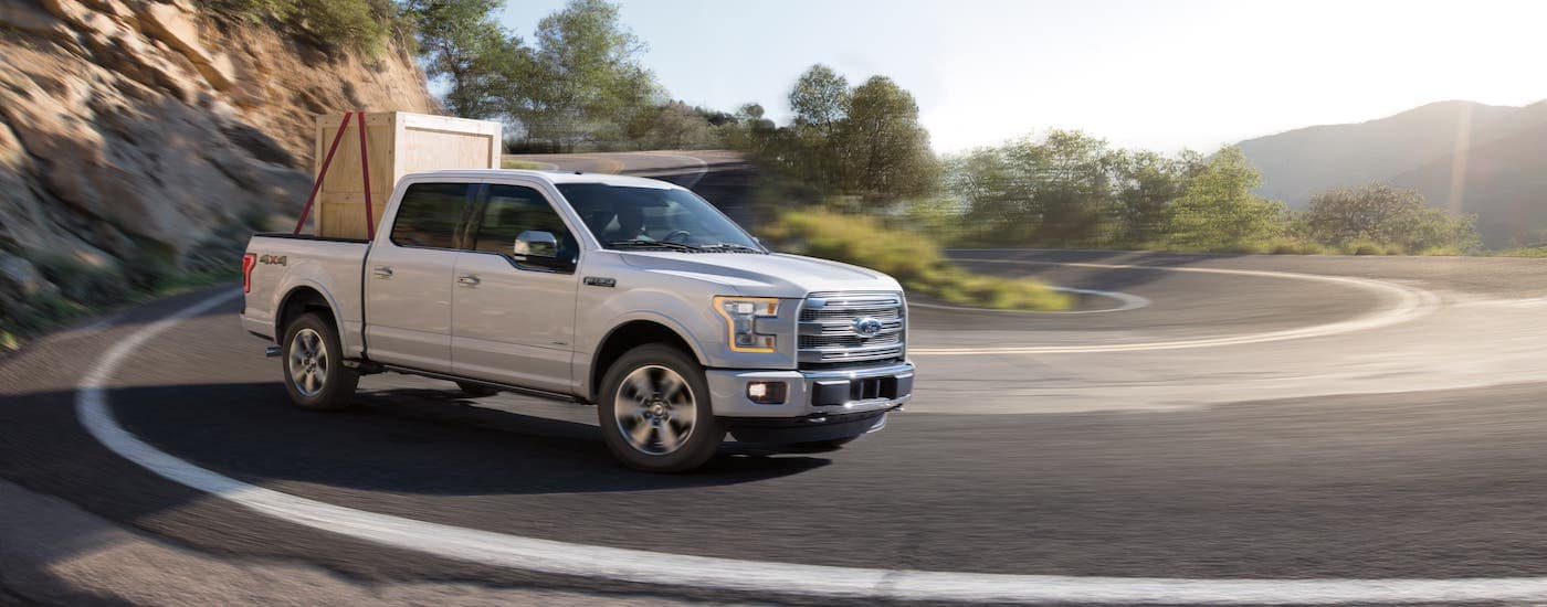 A white 2015 used Ford F-150 is carrying a box while driving on a highway.