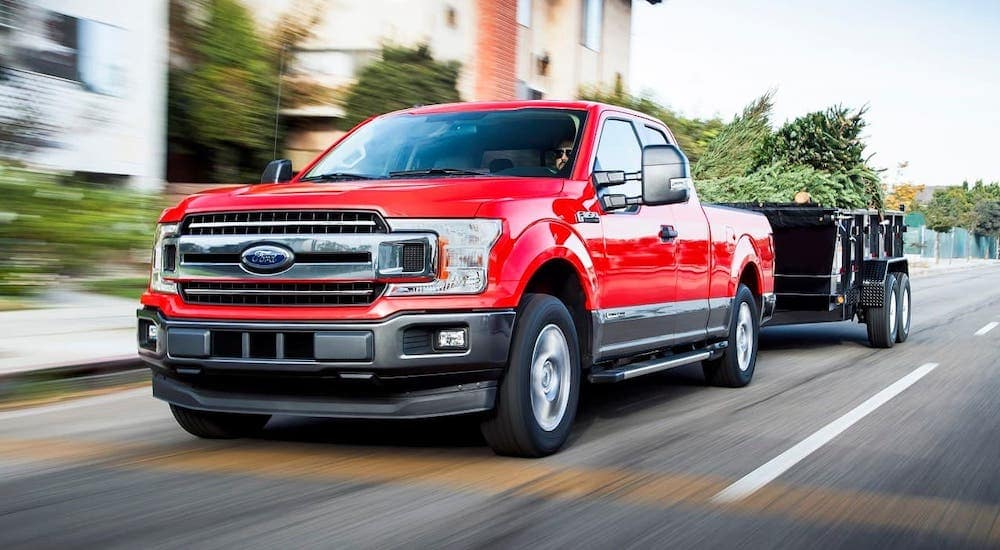 A red 2018 used Ford F-150 Diesel is towing a trailer on a street.