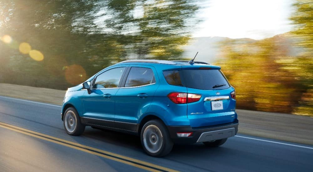 Blue used Ford EcoSport driving on a paved road past trees and mountains
