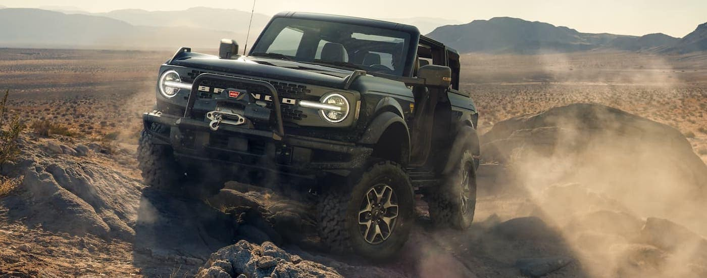 A black 2021 Ford Bronco 2-door is crawling over rocks in a desert after winning the 2021 Ford Bronco (2dr) vs 2020 Jeep Wrangler (2dr) comparison.