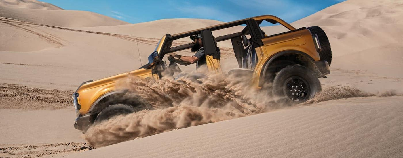 A yellow 2021 Ford Bronco 4-door with no roof or doors is kicking up sand in the dunes.