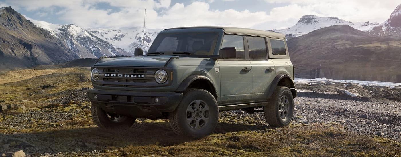 A gray/green 2021 Ford Bronco 4-door is parked in front of distant mountains after winning the 2021 Ford Bronco (4dr) vs 2020 Jeep Wrangler Unlimited comparison.