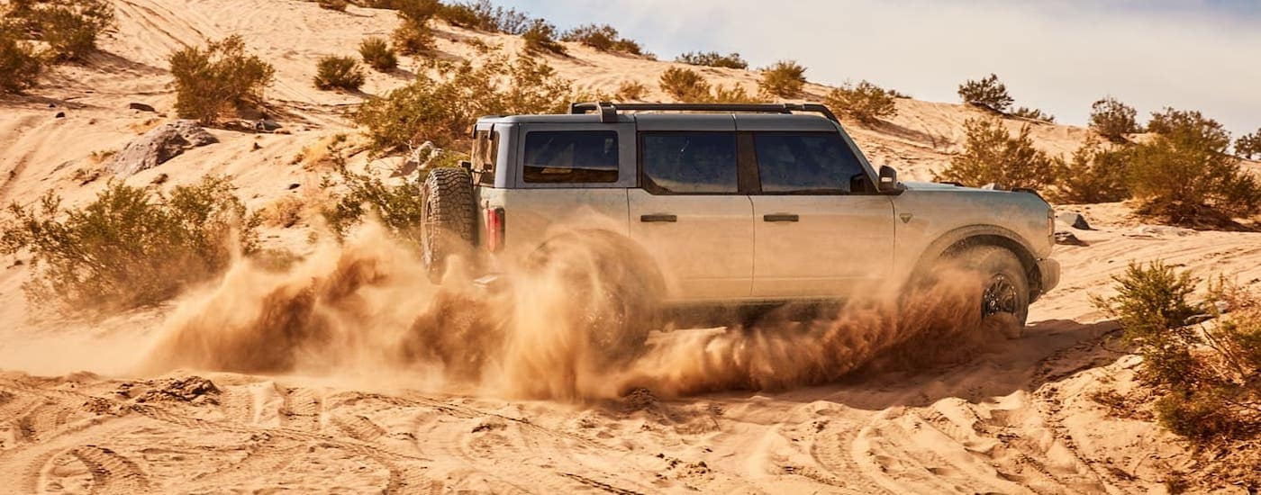 A silver 2021 Ford Bronco 4-door is shown from the side driving in sand piles near Albany, NY.