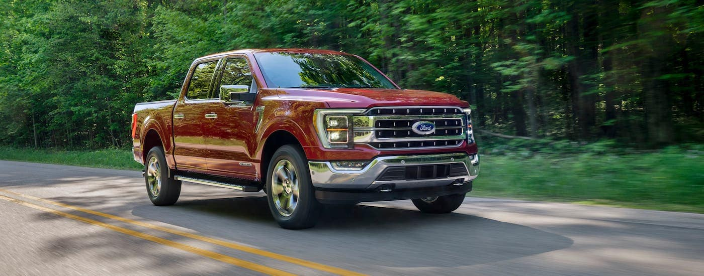 A red 2021 Ford F-150 is driving on a road near Albany as part of the 2021 Ford F-150 vs 2020 Ford F-150 comparison.