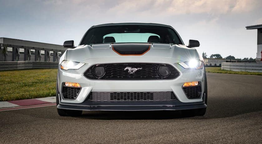 A white 2021 Ford Mustang Mach 1 is shown from the front on a race track.