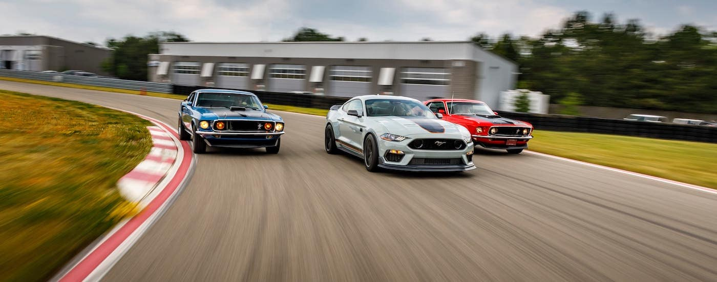 A white 2021 Ford Mustang Mach 1 is flanked by a blue and a red 1960s Mustang Mach 1s on a race track.