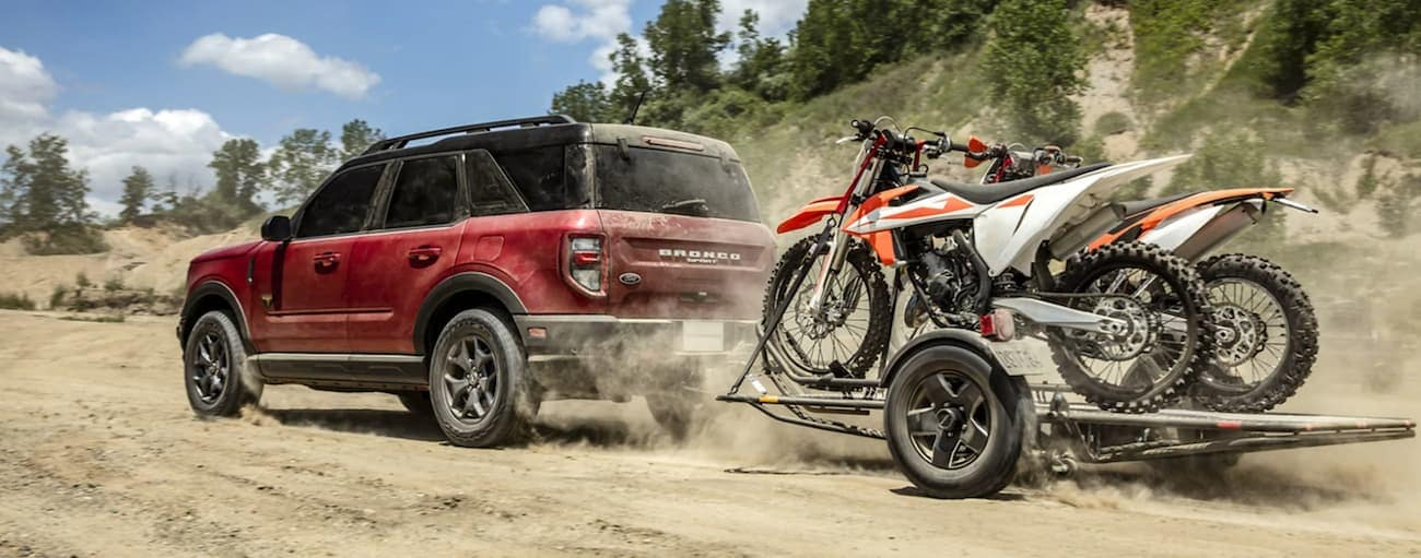 A red 2021 Ford Bronco Sport is driving on a dirt road towing a trailer with dirt bikes.