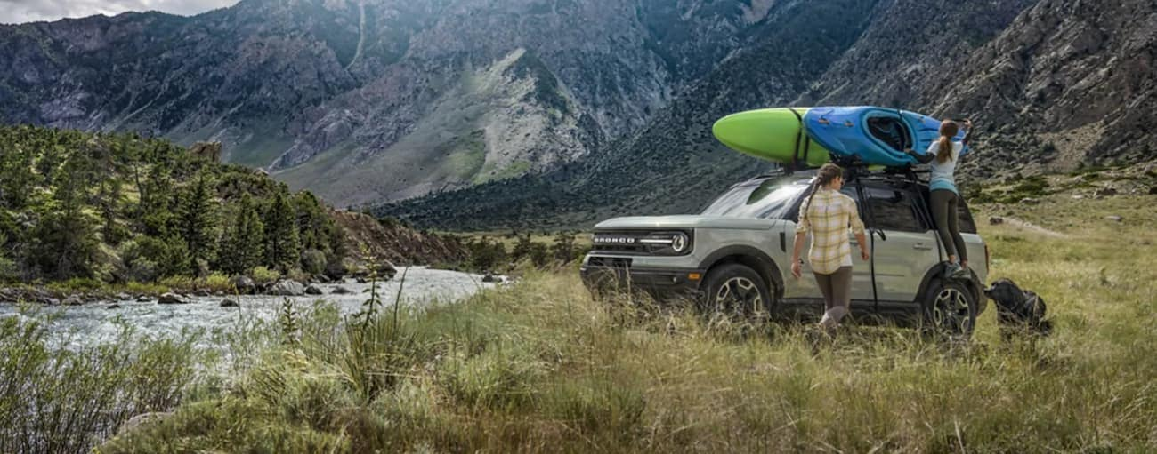 A couple is unloading kayaking gear at a river in a silver 2021 Ford Bronco Sport in the mountains after winning the 2021 Ford Bronco Sport vs 2021 Jeep Renegade comparison.