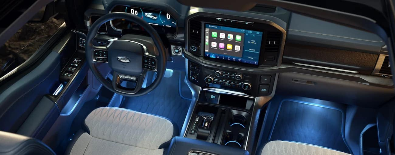 The interior of a 2021 Ford F-150 is shown with blue lighting.