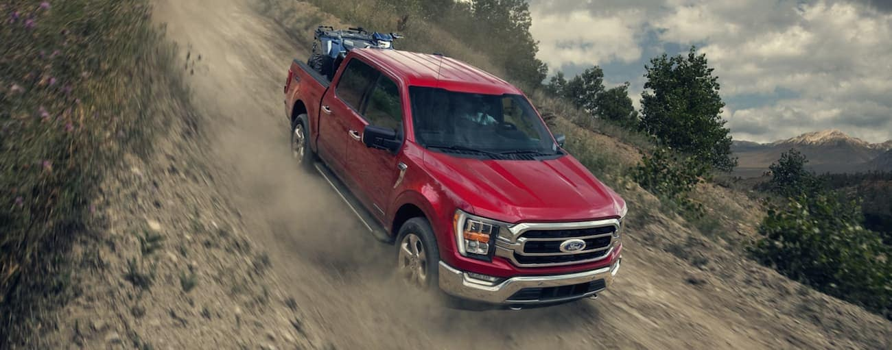 A red 2021 Ford F-150 is driving down a steep dirt hill with a four-wheeler in the bed.
