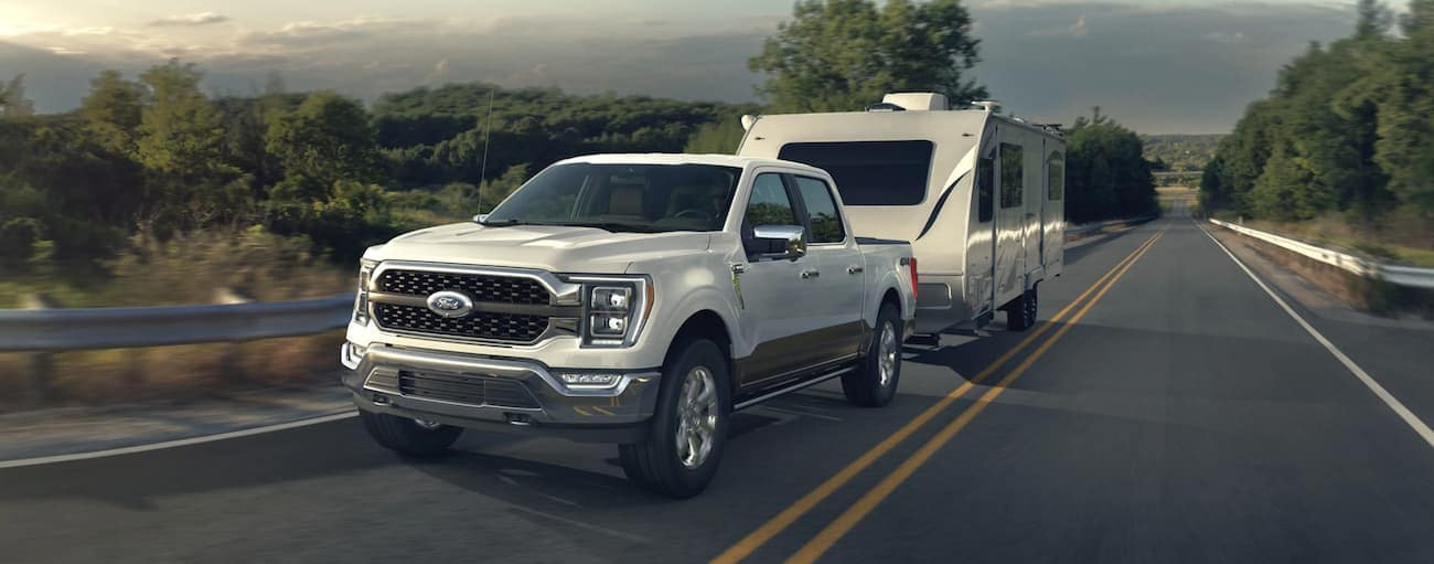 A white 2021 Ford F-150 is towing a camper past trees after wining the 2021 Ford F-150 vs 2021 Chevy Silverado comparison.