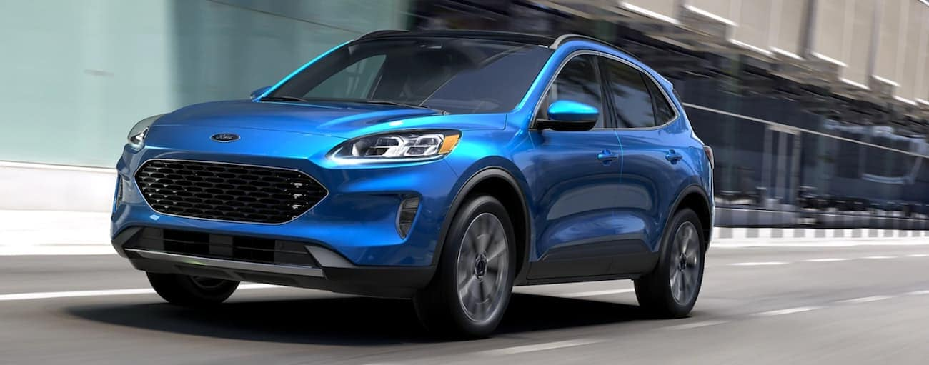 A blue 2020 Ford Escape, which will be similar to the 2021 Ford hybrid and electric models, is driving on a city street.