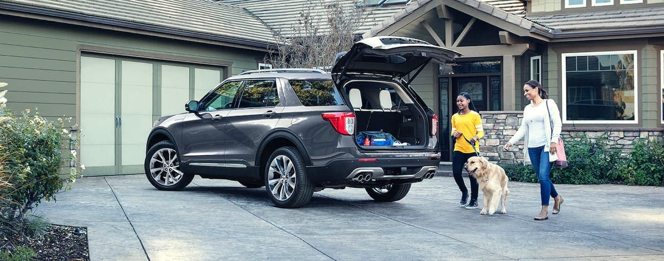 A grey 2021 Ford Explorer with the hatch open is parked at a green house.
