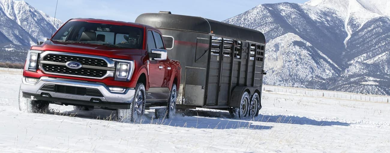 A red 2021 Ford F-150 Hybrid is towing a trailer in the snow.