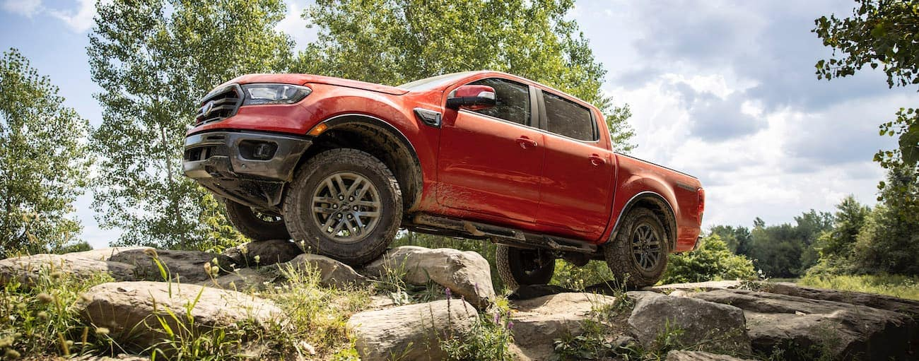 A red 2021 Ford Ranger is off-roading on a rocky trail.