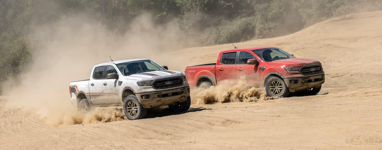 A silver and a red 2021 Ford Ranger Tremor are off-roading on a sand dune.
