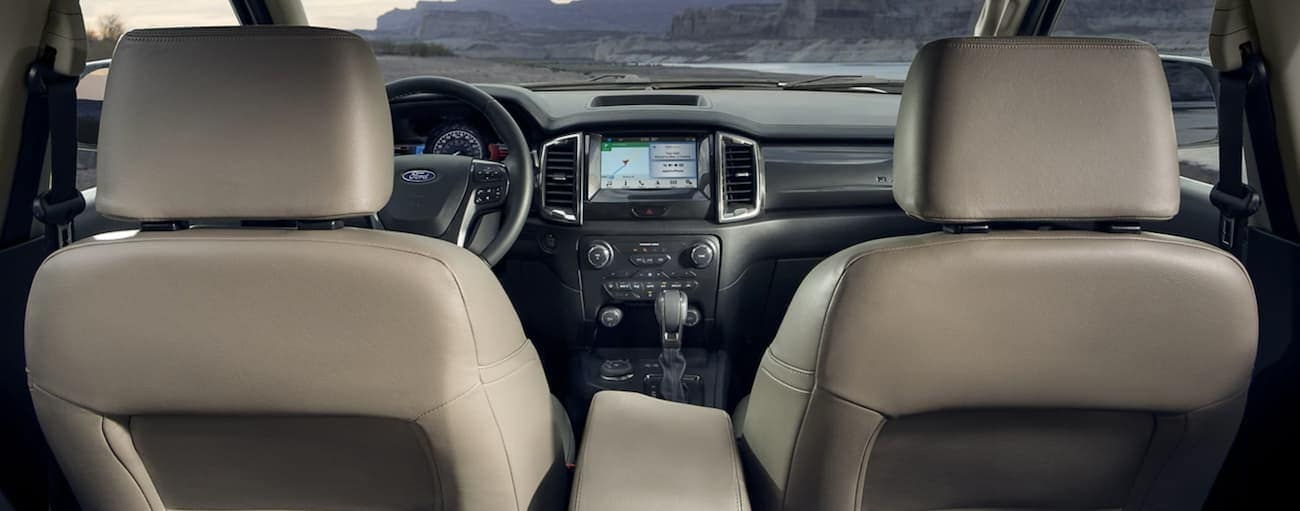 The tan interior of a 2021 Ford Ranger is shown from the back of the front seat forward.