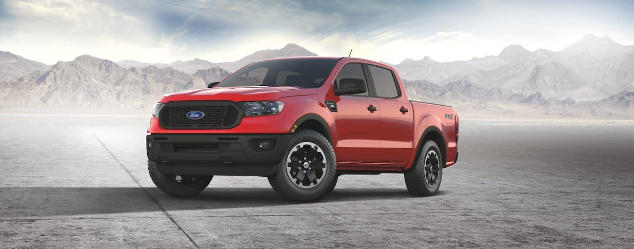 A red 2021 Ford Ranger STX is parked in an open area with distant mountains behind it.