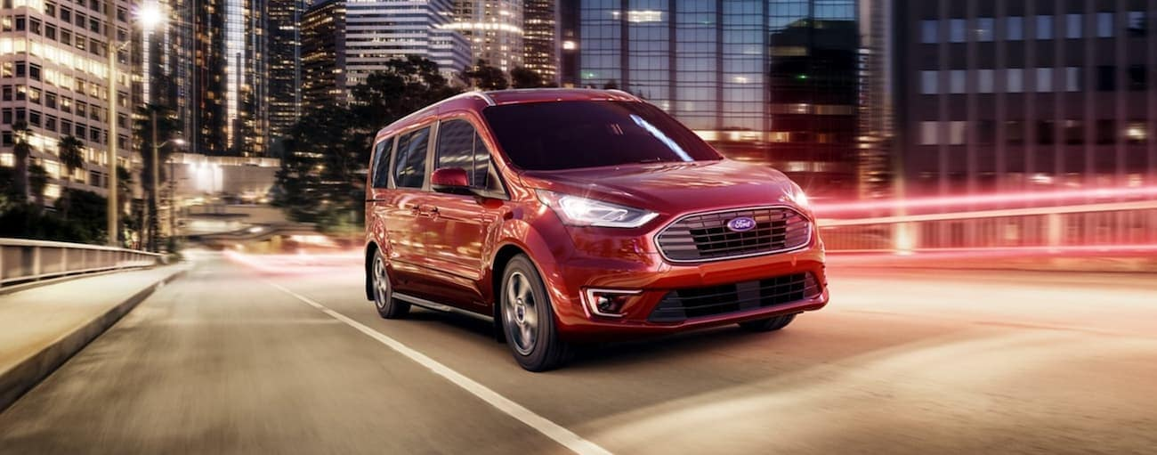 A red 2020 Ford Transit Connect is driving on a city street at night.