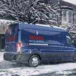 A blue 2020 Ford Transit Cargo is driving over a snowy road.