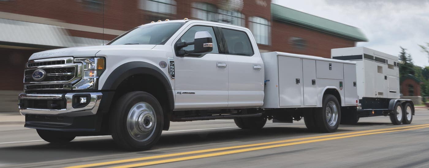 A white 2021 Ford F-550 Chassis Cab is driving on a street after leaving a Ford Commercial Vehicle Dealer in Albany.